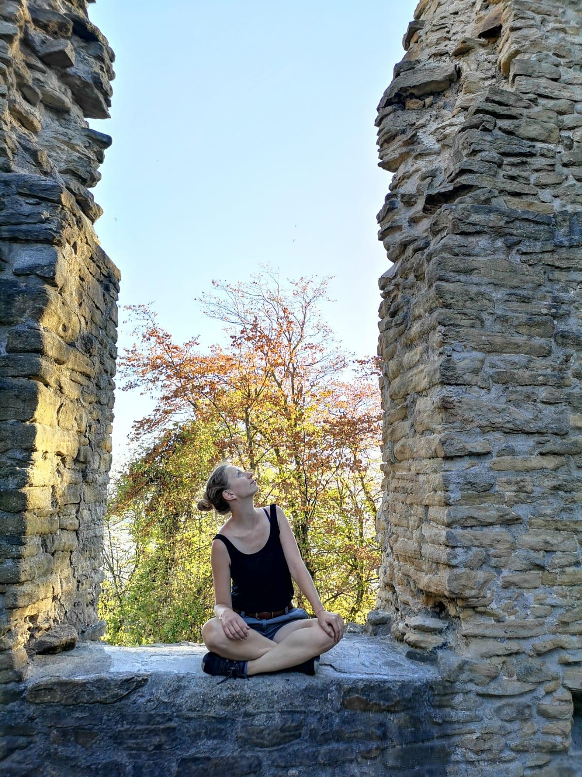 Frau sitzt in Fenster einer Ruine