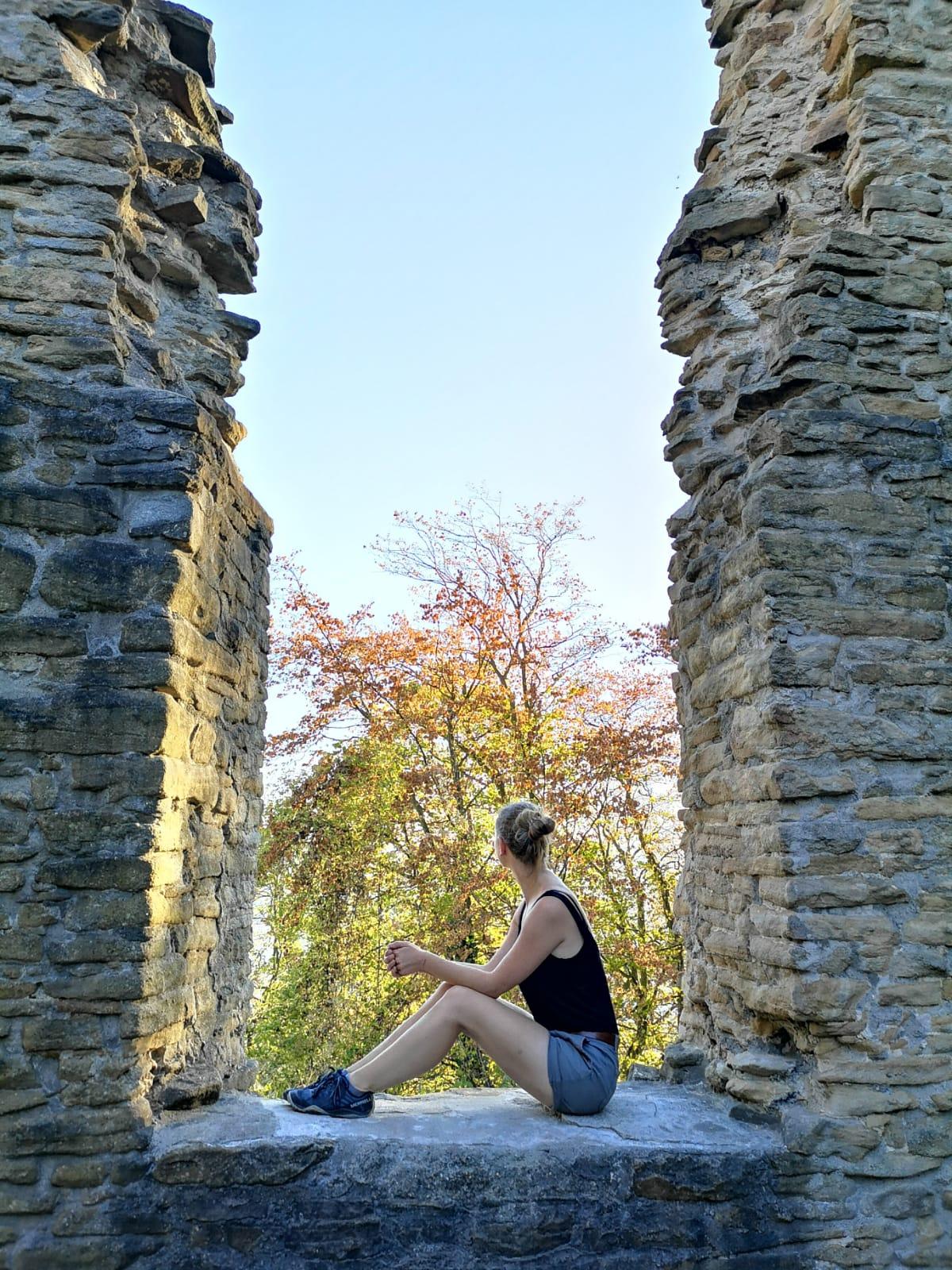 Frau sitzt im Fenster einer Ruine
